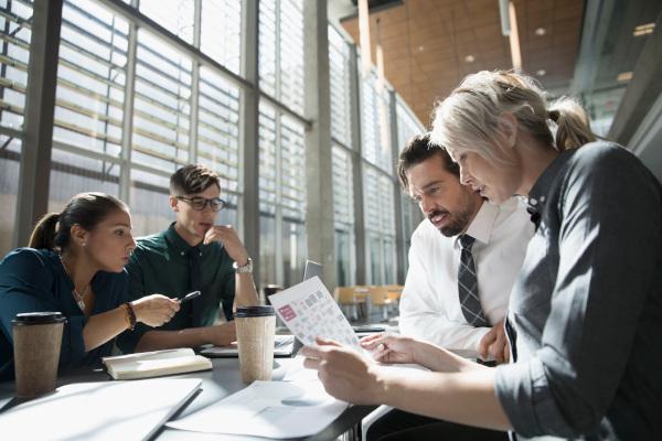 Business people reviewing paperwork in office meeting
