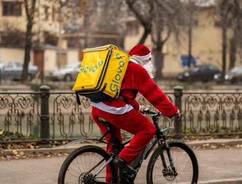 Peste 100 de curieri Glovo vor livra comenzi îmbrăcați în Moș Crăciun în 7 orașe din țară